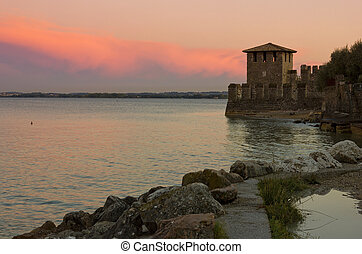 Lake Garda view in Sirmione, Italy with warm red sunset and the tower of The Scaliger Castle in the distance.