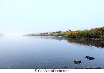 Lake in autumn in misty morning