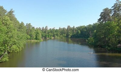 Lake in forest drone view aerial over water flying green tree over water backward push out camera movement