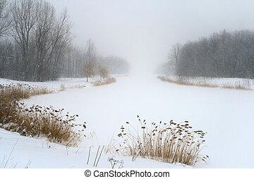 Frozen lake in gloomy misty haze of winter blizzard.