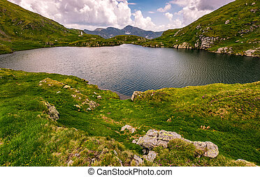 lake in mountains with grass on hillside - clear lake in...