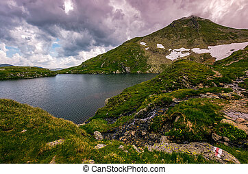 lake in mountains with snow on hillside - clear lake in...