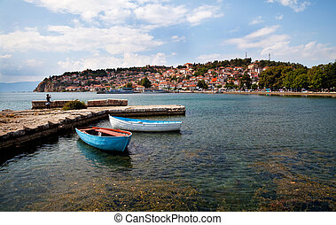 lake in ohrid - two boats by a quay, old town of Ohrid at...