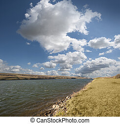 Lake in prairies with clouds and blue sky