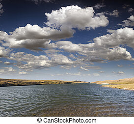 Lake in preairies with clouds and blue sky