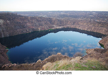 lake in quarry with reflection of clouds