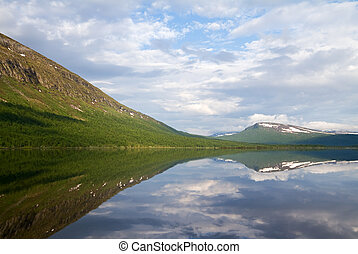 Mountains reflecting in lake in Lapland, Sweden.