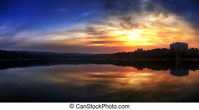 Lake in the mountains at the sunset with mirror reflection on the water