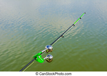 Lake in the mountains. Early morning. Fishing rod with a bell