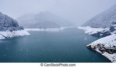 Lake in the mountains in a snowy day