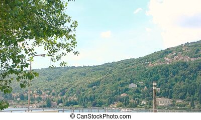 Lake Maggiore, pier. Green mountain and buildings.