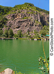 Lake of green water at the foot of the rock with the approach. A place to rest tourists