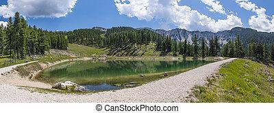 Lake on mountain Petzen with forrest and mountain Hochpetzen...