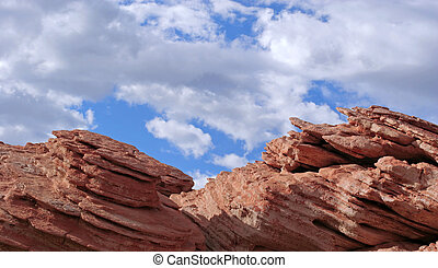 Flat rock formation against blue sky and clouds