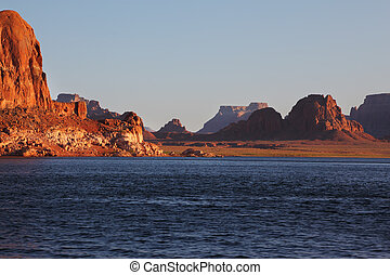Magnificent red sandstone cliffs on the shores of Lake Powell. Arizona, United States, sunset