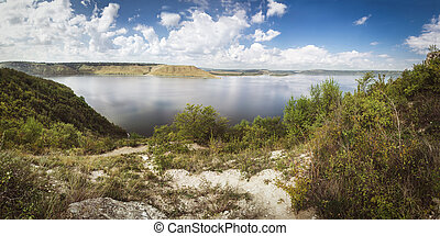 lake shore with forest under sky.