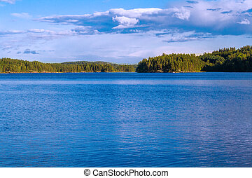 Lake summer view with reflection of clouds on water, Finland