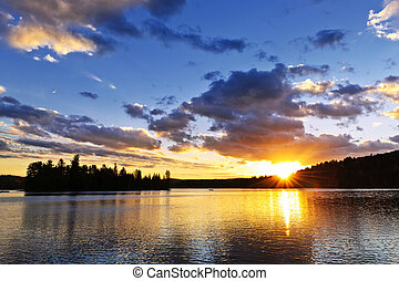 Lake sunset - Sun setting over tranquil lake and forest in...