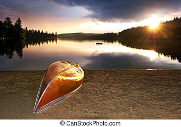 Lake sunset with canoe on beach - Sun setting over tranquil ...