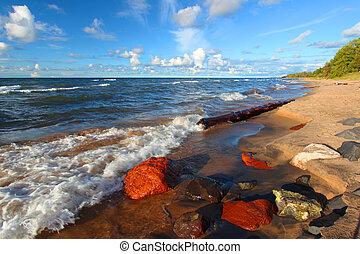 Beach of Lake Superior in northern Michigan under beautiful evening sunlight.
