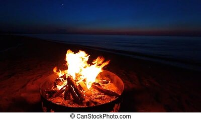 Campfire at sunset along the beautiful beach of Lake Superior in northern Michigan.