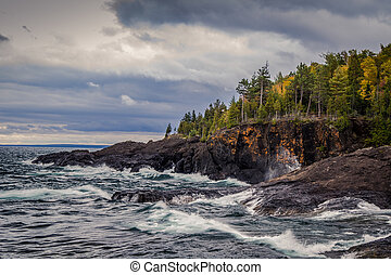 Gray sky and stormy seas crash on the cliffs of the black rocks along the shores of the Lake Superior coast. Presque Isle Park. Marquette, Michigan.