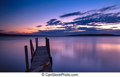Sunrise over the Lake Superior horizon with a dock in the foreground and Grand Island in the background.