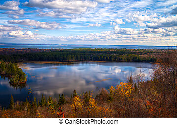 Sweeping panoramic view of an inland lake with blue sky reflections and the great waters of Lake Superior at the horizon. Spectacle Lake Overlook. Brimley, Michigan.