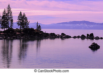 Landscape of Lake Tahoe from shore of silhouette rocks on lake, mountain in background, purple, violet hue