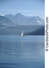 Beautiful, calm scene at the lake of Thun in Switzerland. A boat is sailing in front of the beautiful scenery with the snowy mountains.