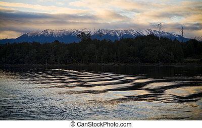 Lake water with snow capped mountains at sunrise