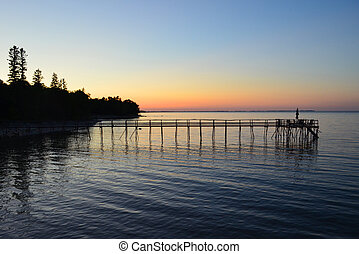 A homemade pier off the shore into Lake Winnipeg at sunset.