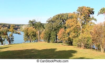 lake with big trees on the banks in autumn