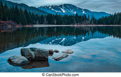 Whistler mountain reflected in lost lake with a blue hue.
