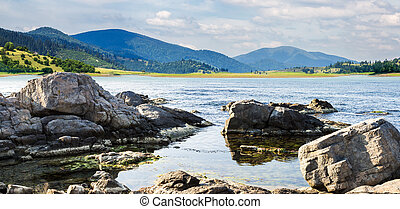 lake with boulders in mountains