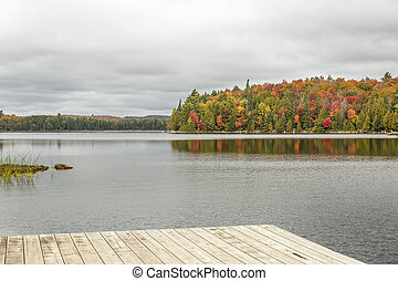 Lake with Fall Colours and Dock in the Foreground - Algonquin Provincial Park, Ontario, Canada