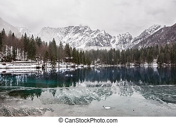 lake with green forest and snowy mountains in the background and skyfall effect. Italian lake during winter with mountains reflections