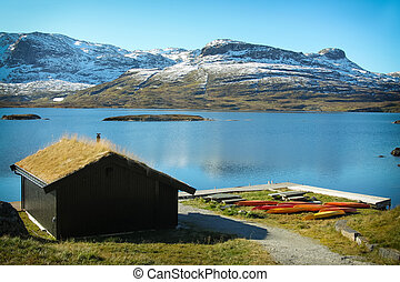 Lake with snow covered mountains and grass roofed shack with colorful kayaks along the wooden pier in the Telemark region Norway, Scandinavia