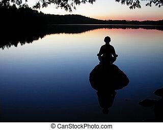 lake yoga - woman meditating on rock