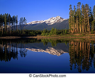 LakeDillon - Mountain peaks and trees reflecting in Lake...