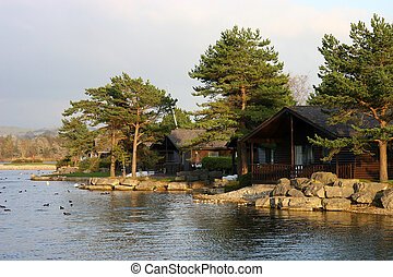 lakeside chalets - wooden chalets among the trees at the...
