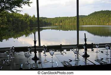 The table is set for a dinner on a screened porch overlooking a lake in Quebec,