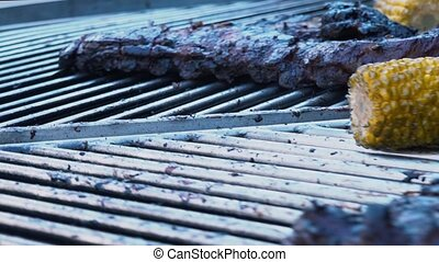 Lamb Ribs and Vegetables on a Rotating Grill, meat and corn on a barbecue, slow motion