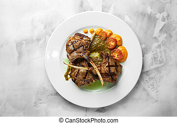 Lamb ribs grilled on cutting board with roasted vegetables. Close up.