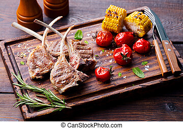 Lamb ribs grilled on cutting board with roasted vegetables.