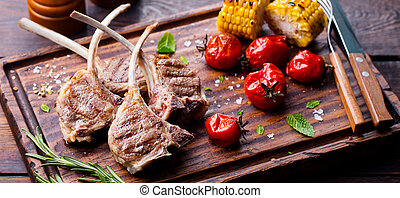Lamb ribs grilled on cutting board with roasted vegetables. Wooden background.