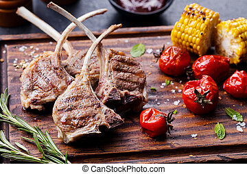 Lamb ribs grilled on cutting board with vegetables
