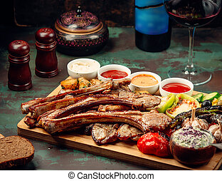 lamb ribs kebab with grilled vegetables and sauces on wood serving board