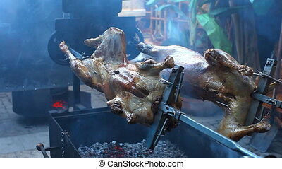 Lamb roasting on a spit on an open outdoor oven