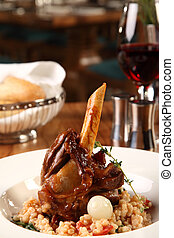 Restaurant table with lamb shank served